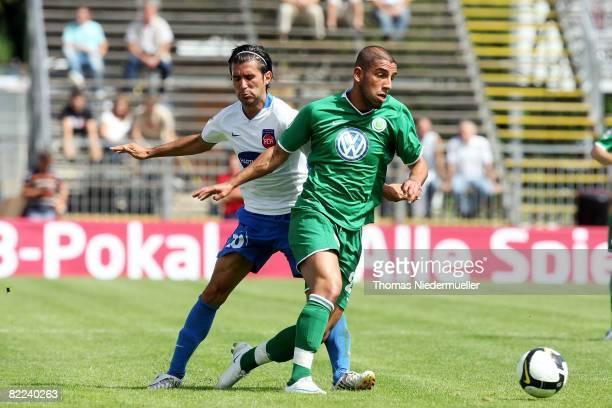 Alper Bagceci of Heidenheim fights for the ball with Ashkan Dejagah of Wolfsburg during the DFB Cup first leg match between 1. FC Heidenheim and VfL...
