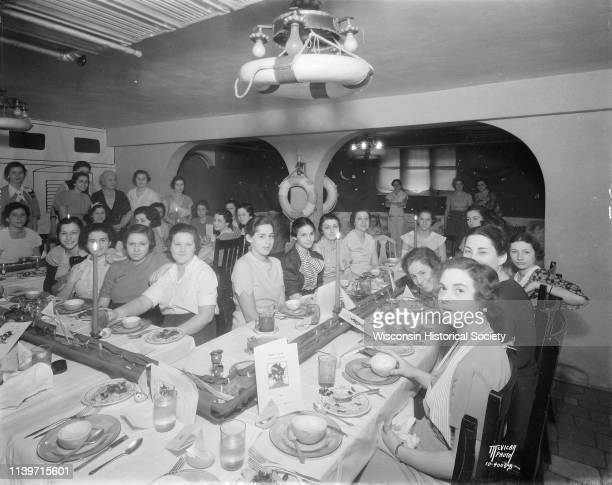 Alpha Epsilon Phi sorority women seated at tables decorated with a marine theme for an informal senior group finishing dinner at 135 Langdon Street...