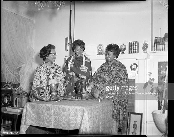 Alpha Kappa Alpha sorority members Nan Currington Edythe Perkins and Janet Thompson wearing African clothing standing behind table with small drum...