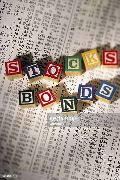 Alphabet blocks on top of newspaper spell stocks and bonds