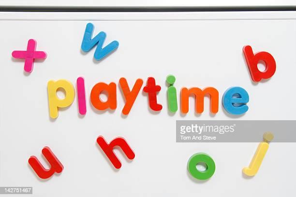 Alphabet fridge magnets spelling 'playtime'