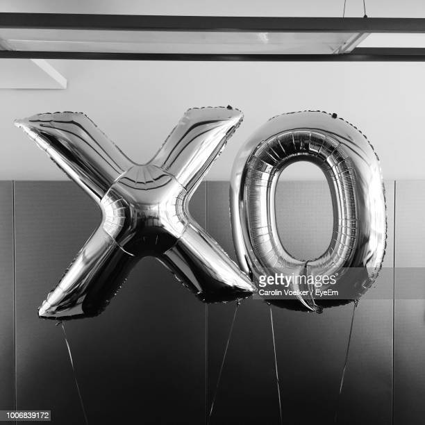 alphabet helium balloons against wall - helium balloon stock pictures, royalty-free photos & images