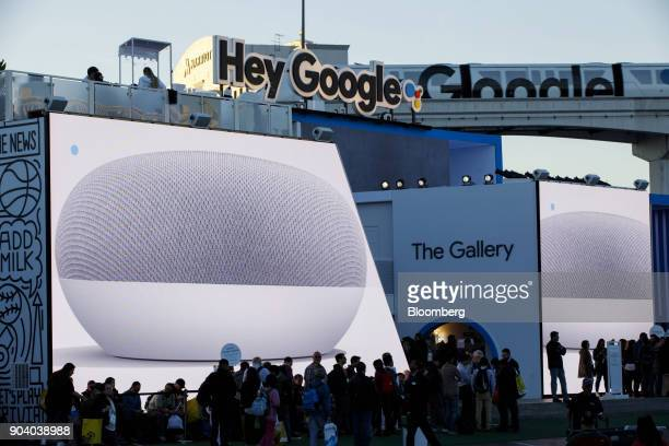 Alphabet Inc's Google Home Mini smart speakers are displayed on screens as attendees stand in line to enter the company's exhibit at the 2018...