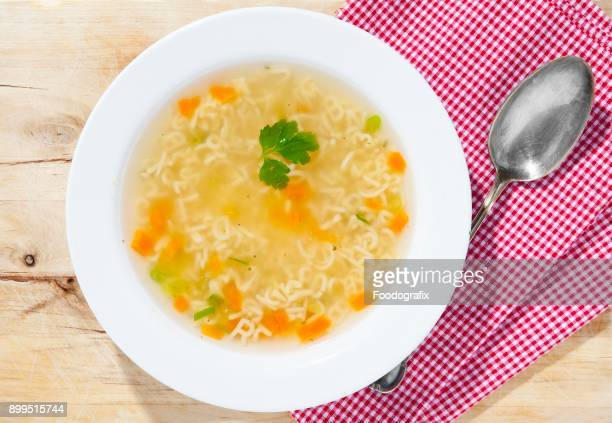 Alphabet soup in a bowl with a spoon on a wooden surface