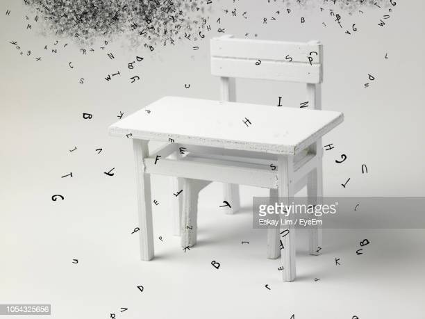 alphabets dissolving over table and chair against white background - dissolving stock pictures, royalty-free photos & images