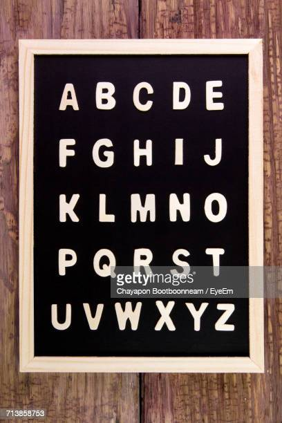 Alphabets On Blackboard At Wooden Table