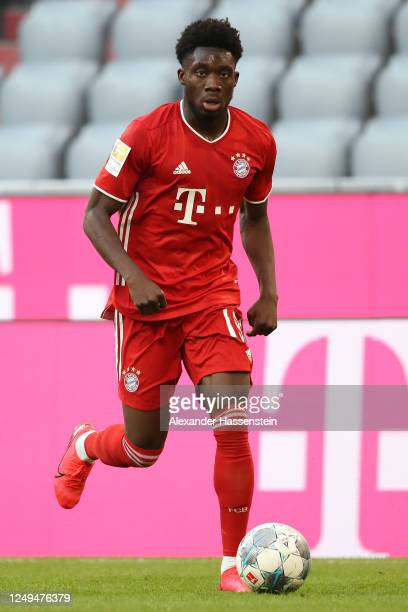 Alphonos Davies of FC Bayern Muenchen runs with the ball during the Bundesliga match between FC Bayern Muenchen and Borussia Moenchengladbach at...