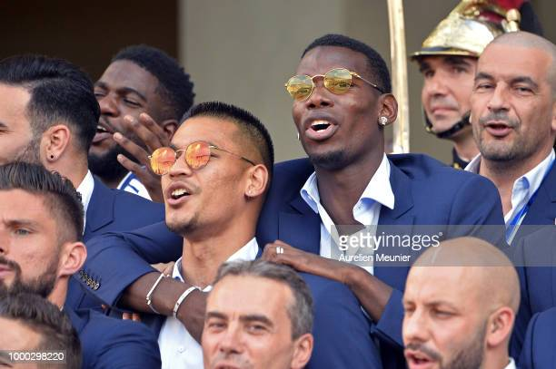Alphonse Areola and Paul Pogba react as French President Emmanuel Macron receives the France football team during a ceremony at the Elysee Palace on...