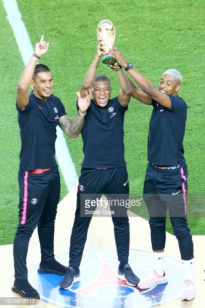 Alphonse Areola Kilian M'Bappe and Presnel Kimpembe of Paris Saint Germain with the trophy of the World Cup during the French Ligue 1 match between...