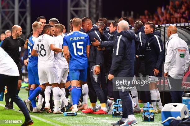 Alphonse Areola of France goes head to head with Holmar Orn Eyjolfsson of Iceland after a foul on Kylian Mbappe of France during the international...