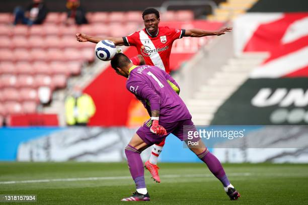 Alphonse Areola of Fulham heads clear as Nathan Tella of Southampton attempts to control the ball during the Premier League match between Southampton...