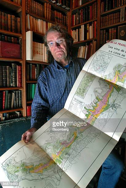 Alphonse Chavroche owner of an antiquarian bookshop, poses with a copy of a map showing the location of the original AOC classified wines of the...