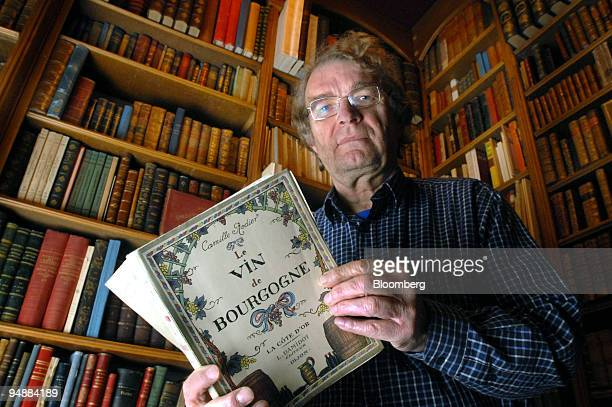 Alphonse Chavroche owner of an antiquarian bookshop, poses with an early guide to the local wines of the Burgundy region in his shop in Beaune,...