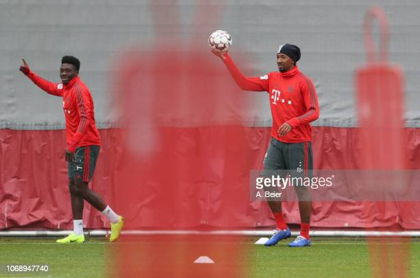 Alphonso Davies and Jerome Boateng of FC Bayern Muenchen joke during a training session at Saebener Strasse training ground on December 6 2018 in...