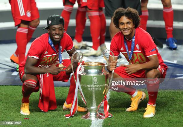 Alphonso Davies and Joshua Zirkzee of FC Bayern Munich pose for a photo with the UEFA Champions League Trophy following their team's victory in the...