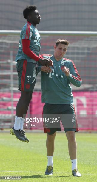Alphonso Davies and Niklas Suele of FC Bayern Muenchen joke during a training session at the club's Saebener Strasse training ground on May 02 2019...