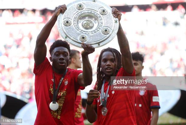 Alphonso Davies and Renato Sanches of Bayern Munich lift the trophy following the Bundesliga match between FC Bayern Muenchen and Eintracht Frankfurt...