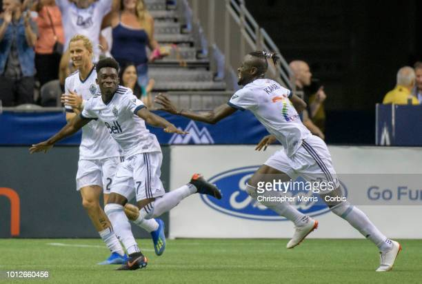 Alphonso Davies and teammates Kei Kamara and Brek Shea of the Vancouver Whitecaps celebrate a goal against Minnesota United at BC Place on July 28...