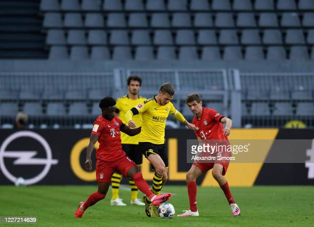 Alphonso Davies and Thomas Mueller of Bayern Muenchen battle for the ball with Lukasz Piszczek of Borussia Dortmund during the Bundesliga match...