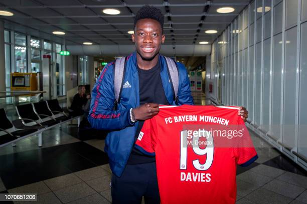 Alphonso Davies holds a jersey showing his shirt number 19 and his surname after his arrival at Munich International Airport on November 21 2018 in...