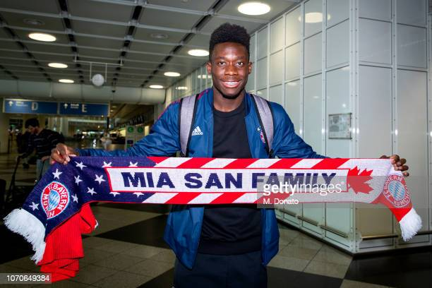 Alphonso Davies holds a scarf showing the words 'Mia san family' which means 'we are family' after his arrival at Munich International Airport on...