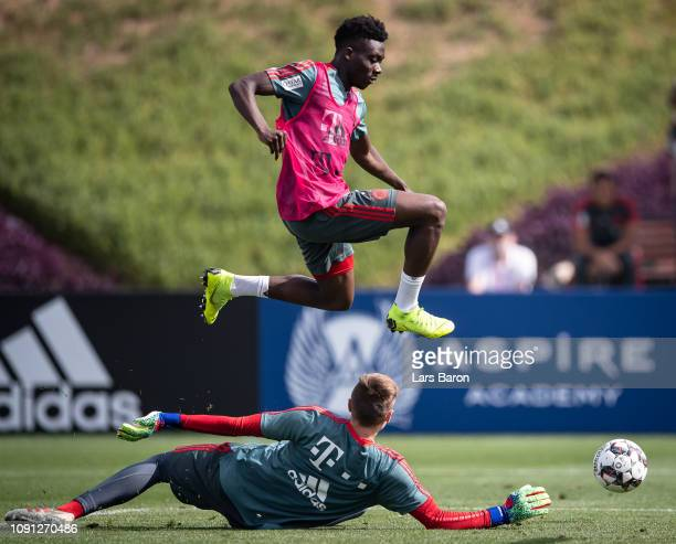 Alphonso Davies jumps over Christian Fruechtl during a training session at day five of the Bayern Muenchen training camp at Aspire Academy on January...