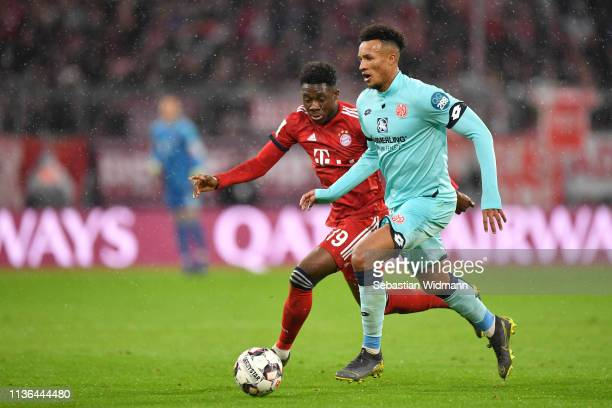 Alphonso Davies of Bayern Munich and JeanPhilippe Gbamin of Mainz compete for the ball during the Bundesliga match between FC Bayern Muenchen and 1...