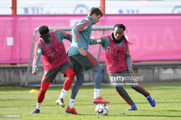 Alphonso Davies of Bayern Munich and Renato Sanches compete with Thomas Mueller for the ball during a FC Bayern Muenchen training session at Saebener...