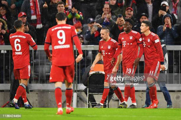 Alphonso Davies of Bayern Munich celebrates scoring his teams sixth goal of the game with team mates during the Bundesliga match between FC Bayern...