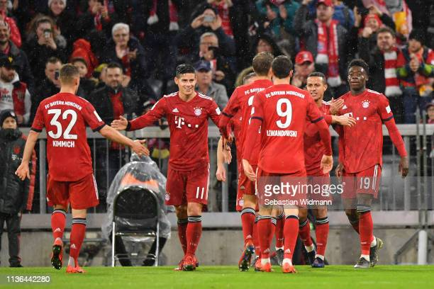 Alphonso Davies of Bayern Munich celebrates scoring his teams sixth goal with teammates during the Bundesliga match between FC Bayern Muenchen and 1...
