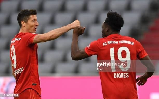 Alphonso Davies of Bayern Munich celebrates with Robert Lewandowski after scoring his team's fifth goal during the Bundesliga match between FC Bayern...