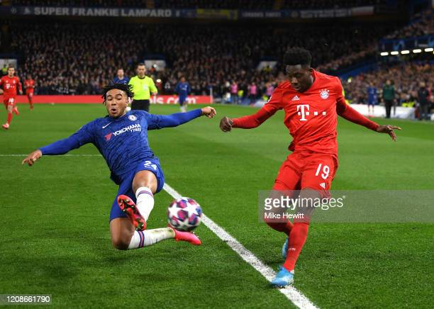 Alphonso Davies of Bayern Munich crosses under pressure from Reece James of Chelsea during the UEFA Champions League round of 16 first leg match...