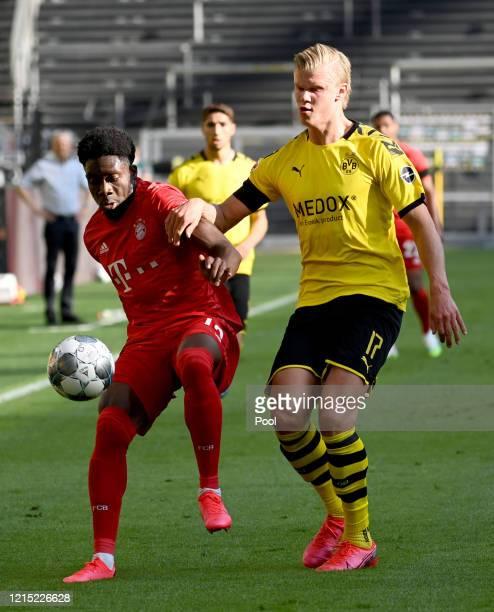 Alphonso Davies of Bayern Munich is challenged by Erling Haaland of Borussia Dortmund during the Bundesliga match between Borussia Dortmund and FC...