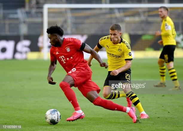 Alphonso Davies of Bayern Munich is challenged by Thorgan Hazard of Borussia Dortmund during the Bundesliga match between Borussia Dortmund and FC...