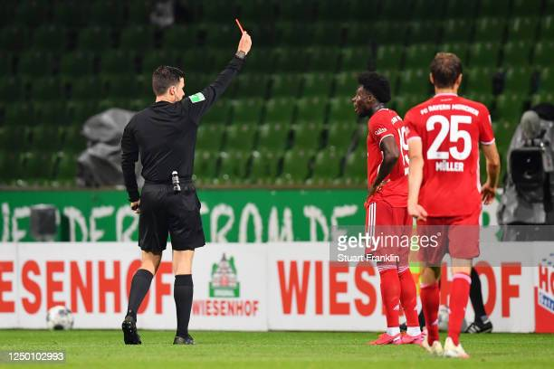 Alphonso Davies of Bayern Munich is shown a red card by referee Harm Osmers during the Bundesliga match between SV Werder Bremen and FC Bayern...