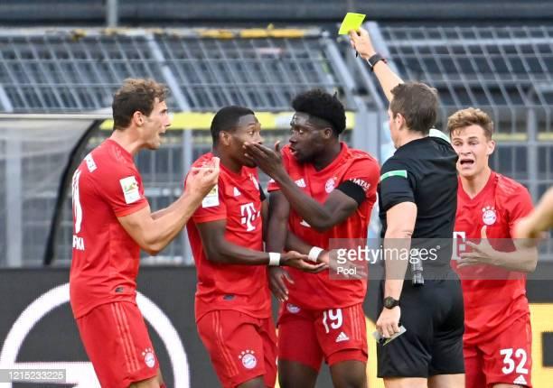 Alphonso Davies of Bayern Munich is shown a yellow card by Referee Tobias Stieler during the Bundesliga match between Borussia Dortmund and FC Bayern...