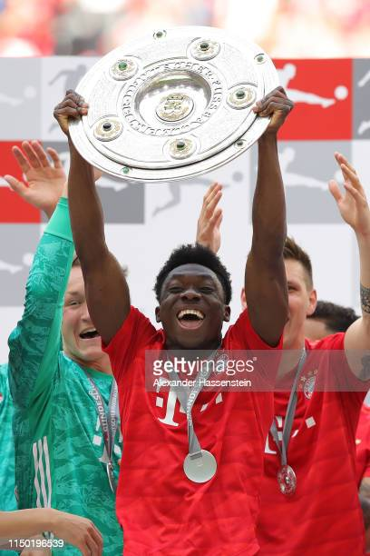 Alphonso Davies of Bayern Munich lifts the trophy following the Bundesliga match between FC Bayern Muenchen and Eintracht Frankfurt at Allianz Arena...