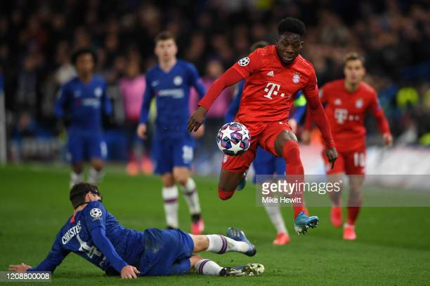 Alphonso Davies of Bayern Munich skips past a challenge Andreas Christensen of Chelsea during the UEFA Champions League round of 16 first leg match...