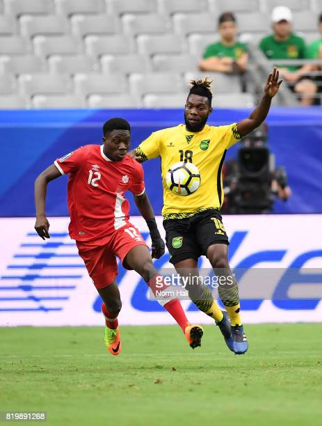Alphonso Davies of Canada battles for possession with Owayne Gordon of Jamaica during the first half in a quarterfinal match during the CONCACAF Gold...