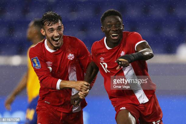 Alphonso Davies of Canada celebrates with teammate Russell Tilbert after scoring the fourth goal of his team during the Group A match between French...
