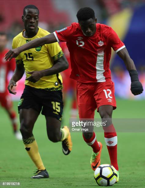 Alphonso Davies of Canada fights for the ball with JeVaughn Watson of Jamaica during the CONCACAF Gold Cup Quarterfinal match between Jamaica and...