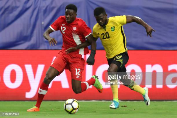 Alphonso Davies of Canada fights for the ball with Kemar Lawrence of Jamaica during the CONCACAF Gold Cup Quarterfinal match between Jamaica and...