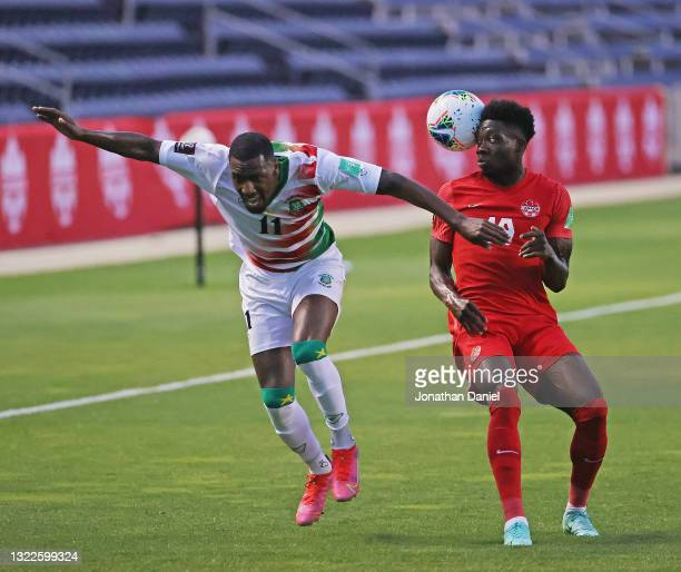 Alphonso Davies of Canada heads the ball away from the ball Sheraldo Becker of Suriname during a FIFA World Cup Qualifier at SeatGeek Stadium on June...