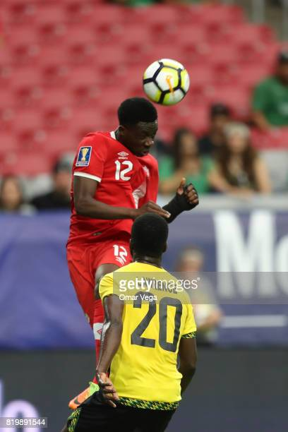 Alphonso Davies of Canada jumps for a header with Kemar Lawrence of Jamaica during the CONCACAF Gold Cup Quarterfinal match between Jamaica and...