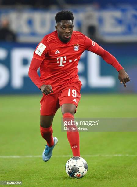 Alphonso Davies of FC Bayern München controls the ball during the DFB Cup quarterfinal match between FC Schalke 04 and FC Bayern Muenchen at Veltins...