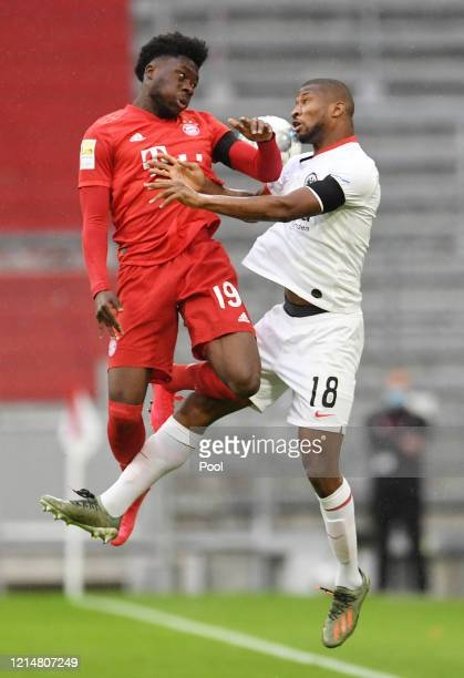 Alphonso Davies of FC Bayern Muenchen battles for possession with Almamy Toure of Eintracht Frankfurt during the Bundesliga match between FC Bayern...