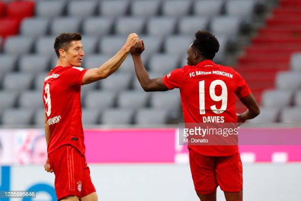 Alphonso Davies of FC Bayern Muenchen celebrates after scoring his team's fifth goal with team mate Robert Lewandowski during the Bundesliga match...
