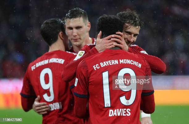 Alphonso Davies of FC Bayern Muenchen celebrates his first goal for Bayern Muenchen with teammate Leon Goretzka during the Bundesliga match between...