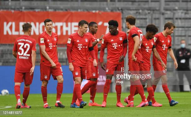 Alphonso Davies of FC Bayern Muenchen celebrates with his team mates after scoring his team's fourth goal during the Bundesliga match between FC...