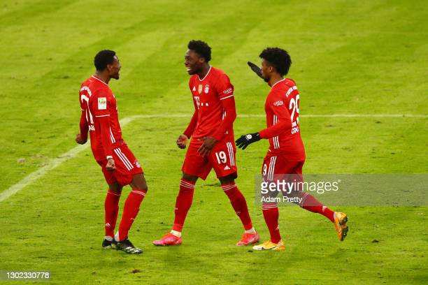 Alphonso Davies of FC Bayern Muenchen celebrates with teammates David Alaba and Kingsley Coman after scoring their team's third goal during the...
